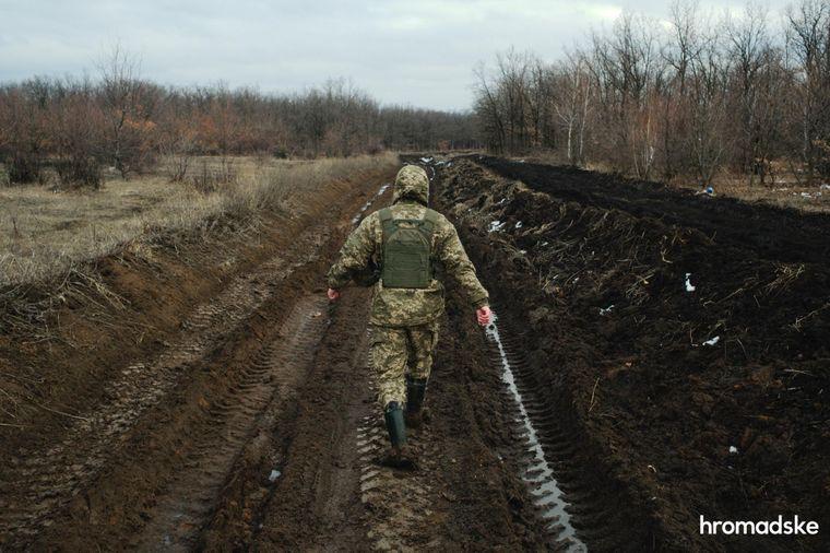 Військовий показує шлях до села Новоолександрівка ґрунтовою дорогою, якою звичайний транспорт не зможе проїхати
