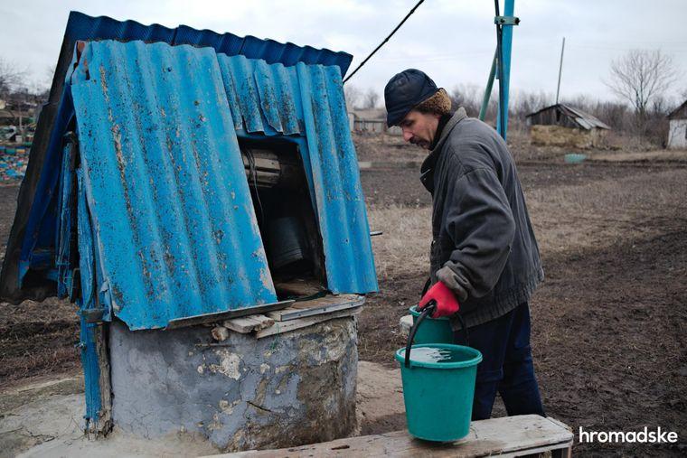 Микола Миколайович набирає воду з колодязя біля свого будинку в Новоолександрівці