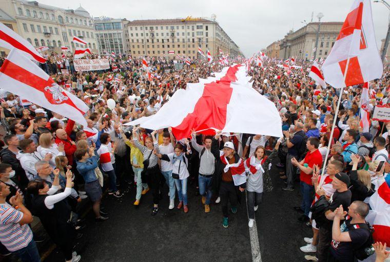 Демонстранти несуть величезний історичний прапор Білорусі, коли тисячі людей збираються на акцію протесту на Майдані Незалежності в Мінську, Білорусь, 23 серпня 2020 року.