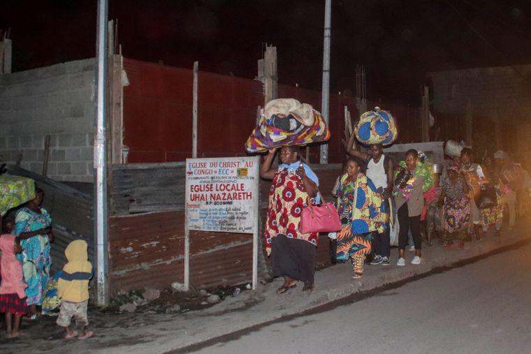 Люди с вещами бегут от извержения вулкана Ньирагонго в Гоме, 22 мая 2021 года
