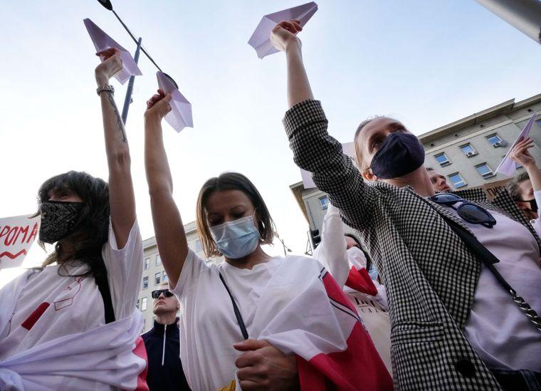 Протестувальники піднімають паперові літаки,вимагаючи свободи для білоруського журналіста Романа Протасевича під час демонстрації перед офісом Європейської комісії у Варшаві, Польща, 24 травня 2021 року.