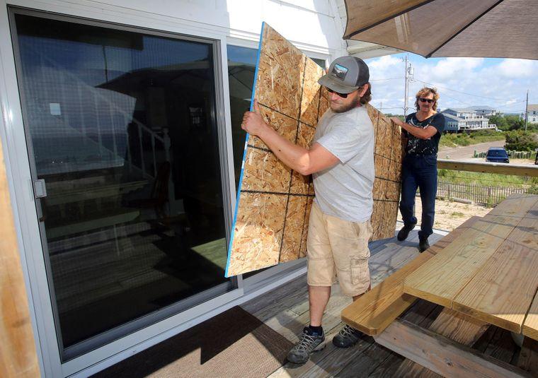 Чоловіки у Чарльзтауні закривають скляні двері, готуючись до можливих наслідків урагану «Генрі»,  21 серпня 2021 року.