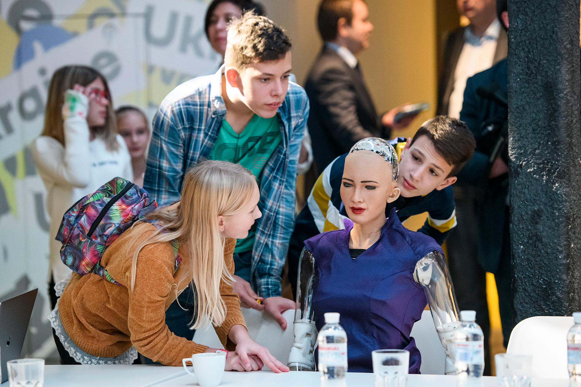 Школярі-винахідники, які займаються робототехнікою, розглядають людиноподібного робота (гіноїда) Софію у Києві, 11 жовтня 2018 року. Софія, розроблена гонконгською компанією Hanson Robotics і спроектована таким чином, щоб вчитися і адаптуватися до поведінки людей, а також співпраці з ними. Вона стала першою у світі роботом, що отримав громадянство будь-якої країни.