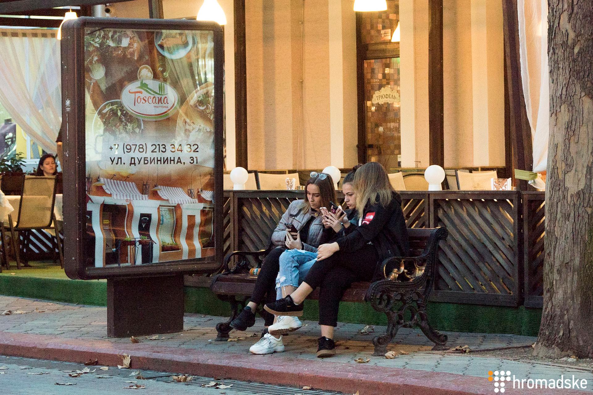 Дівчата в центрі міста перевіряють сторінки у соцмережах в телефоні, Керч, Крим, 22 жовтня 2018 року