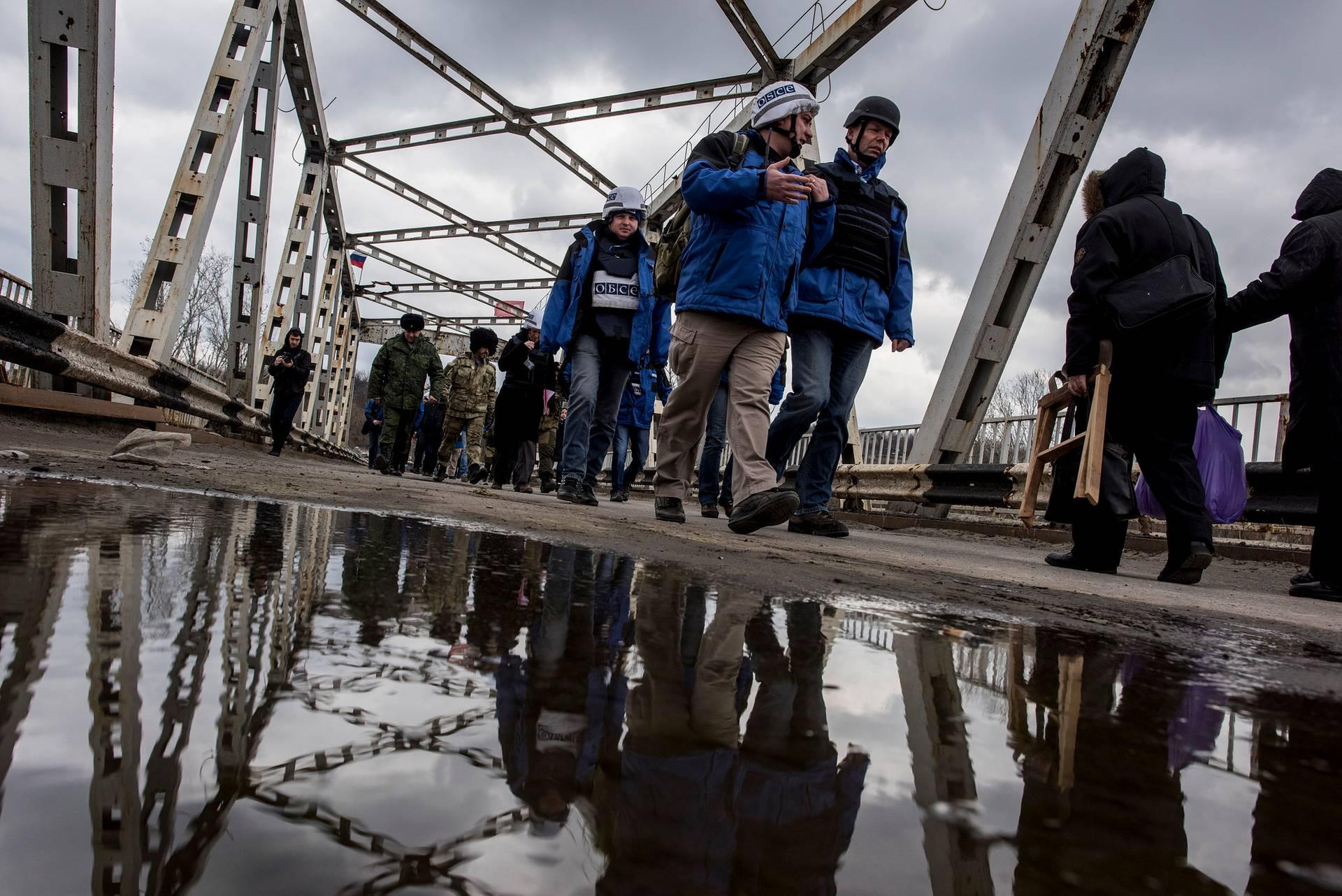 Александр Хуг (праворуч) із спостерігачами місії ОБСЄ у супроводі військових переходить зруйнований міст на КПВВ «Станиця Луганська», Луганська область, 18 березня 2016
