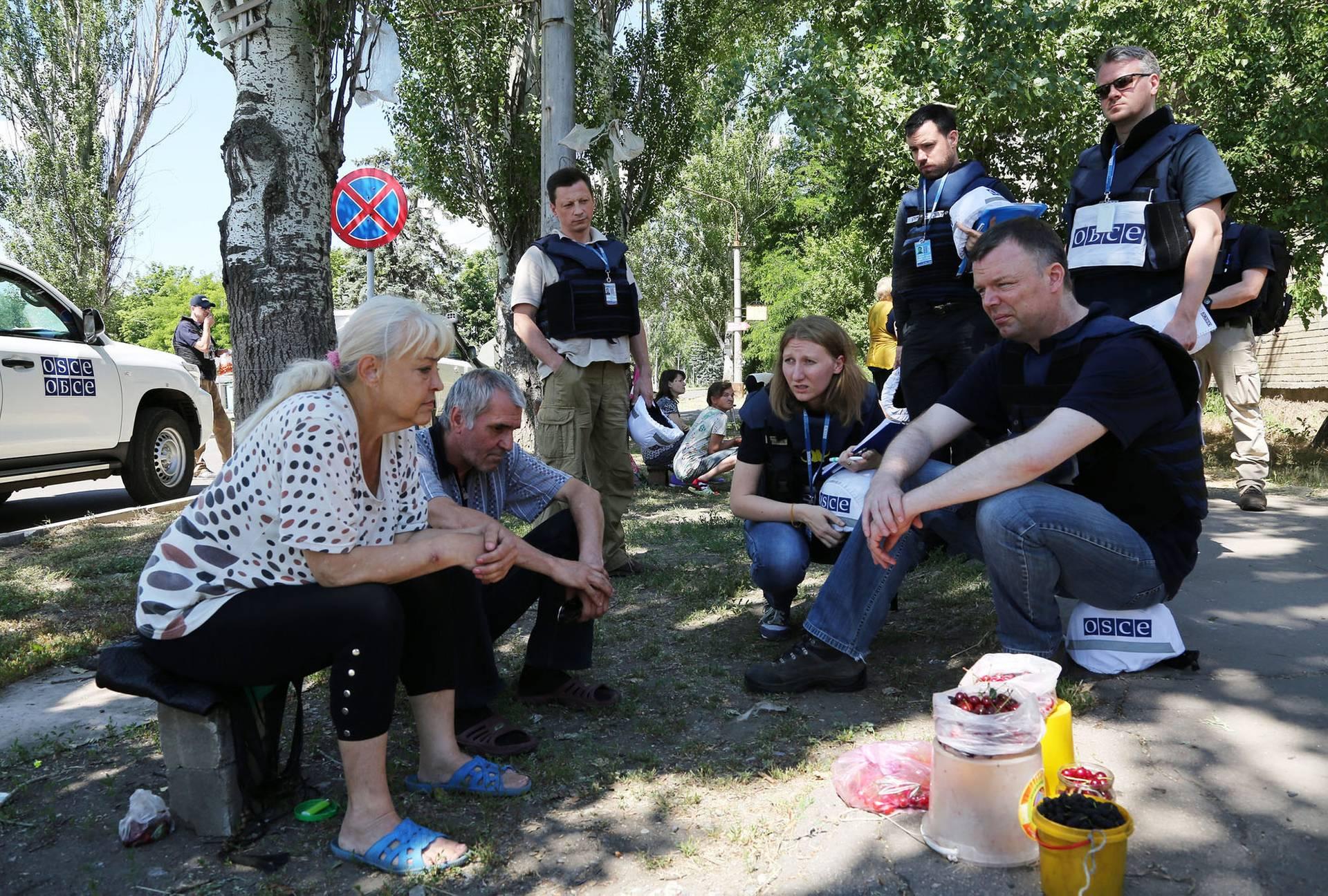 Александр Хуг (праворуч) спілкується з місцевими жителями Красногорівки поблизу лінії розмежування, Донецька область, 21 червня 2017 року
