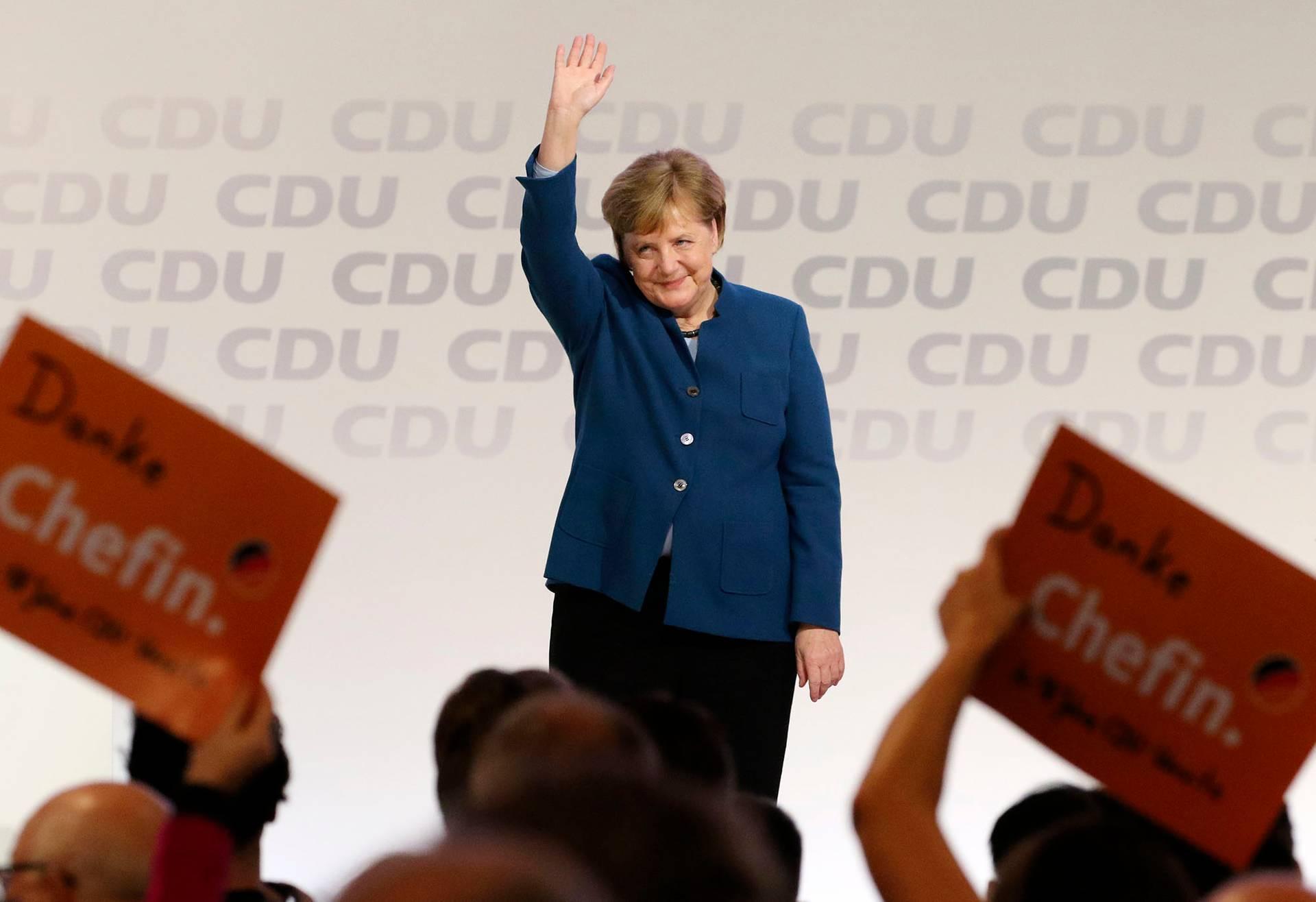 Німецька канцлерка Ангела Меркель дякує всім після свого останього виступу вролі лідерки партії наХристиянсько-Демократичного Союзк (ХДС) уГамбурзі, Німеччина, 7грудня 2018р. Присутні взалі тримають таблички знаписом «Дякуємо, шефине»