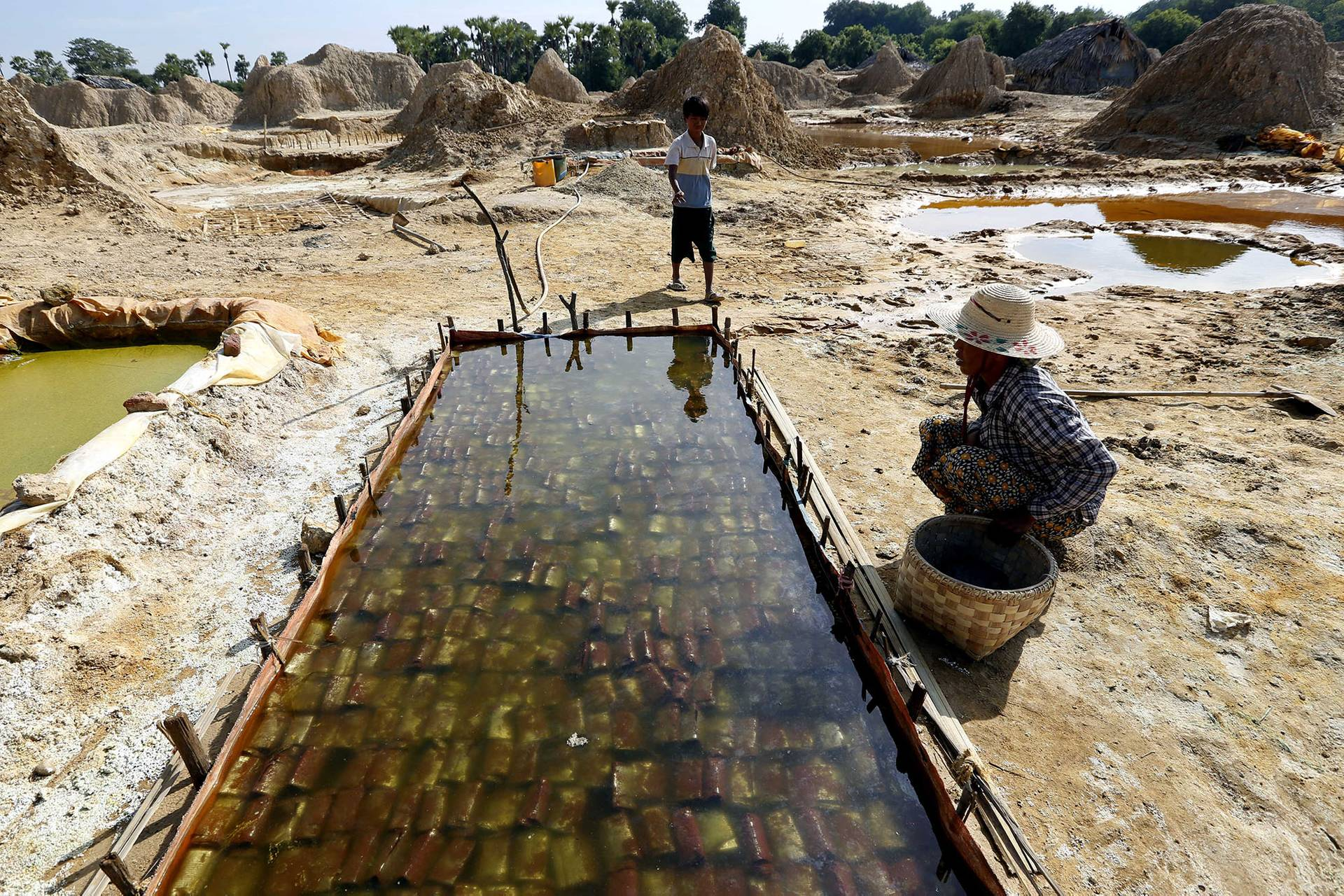 Неповнолітній хлопчик із своєю матір'ю спостерігають за процесом обробки міді на шахті біля містечка Моніва, М'янма, 1 грудня 2012 року. В деяких країнах нерідко використовують дитячу працю на шахтах