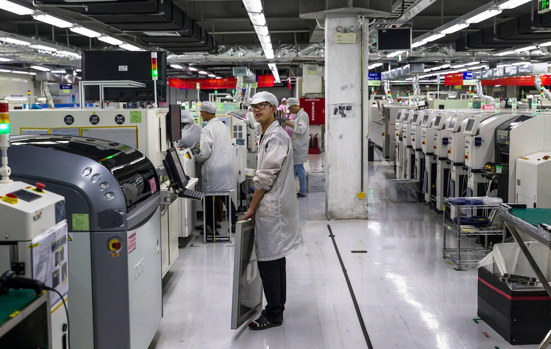 Люди працюють на машинах на заводі Foxconn у місті Ґуйян, провінція Ґуйчжоу, Китай, 28 травня 2018 року. Завод Foxconn у Ґуйяні — головний партнер компанії Apple — випустив 16 мільйонів смартфонів для Nokia та Huawei у 2017 році майже 30 мільйонів у 2018 році. У 2010 році через жорсткі умови праці завод накрила звиля самогубств робітників. Після того, як про це розповіли журналісти керівництво заводу обіцяло покращити умови