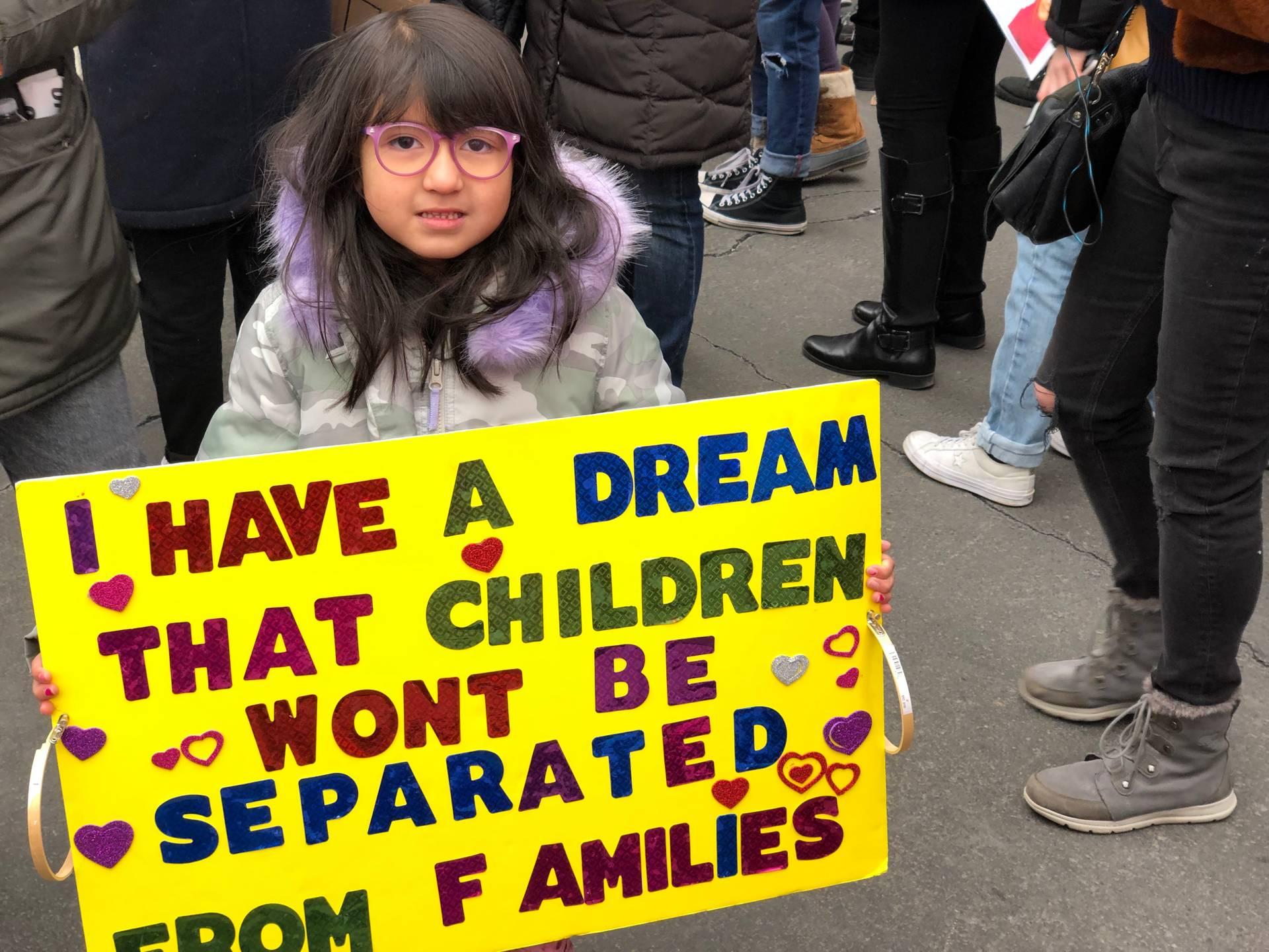 Дівчинка з плакатом I have a dream, that children won't be separated from families «Я мрію, що діти не відділятиму від їхніх родин», — напис на плакаті в руках маленької дівчинки, яку на Жіночу ходу привели батьки-мігранти з Латинської Америки. Він нагадує слова найвідомішої промови легенди руху за права афроамериканців Мартіна Лютера Кінга про мрію жити без расизму, а також введений влітку 2018-го і згодом скасований указ Дональда Трампа про те, що на кордоні зі США дітей мігрантів і шукачів притулку відбирали у батьків. За даними CNN чимало дітей і далі утримуються без рідних. А US Today повідомляє, що сім'ї і далі розділяють.