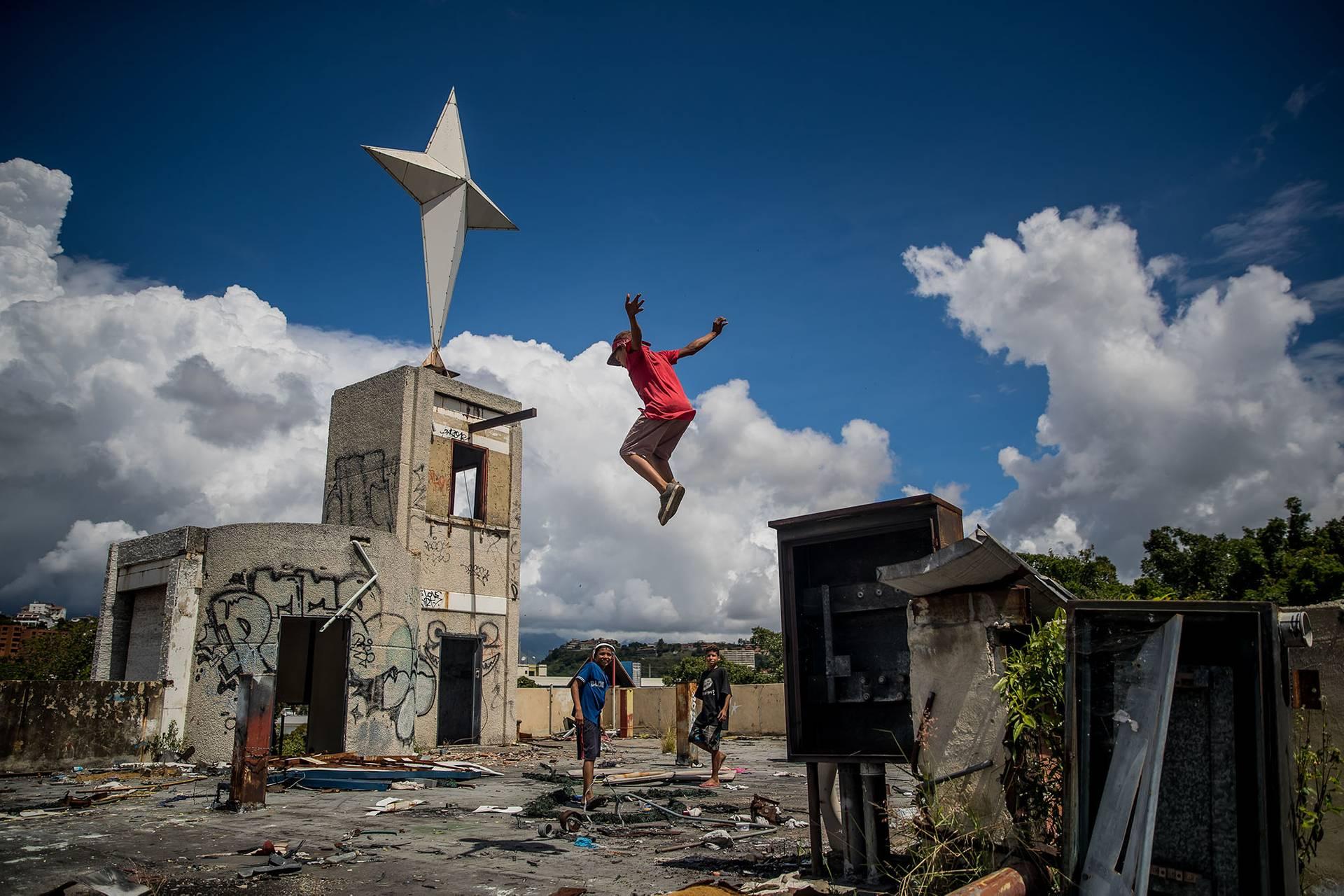 Діти граються на руїнах будівлі казино в районі Ла-Тринідад у Каракасі, Венесуела, 6 листопада 2018 року. За останні роки 3 мільйони венесуельців емігрували через падіння економіки, яке потягнуло за собою значне погіршення рівня життя у країні