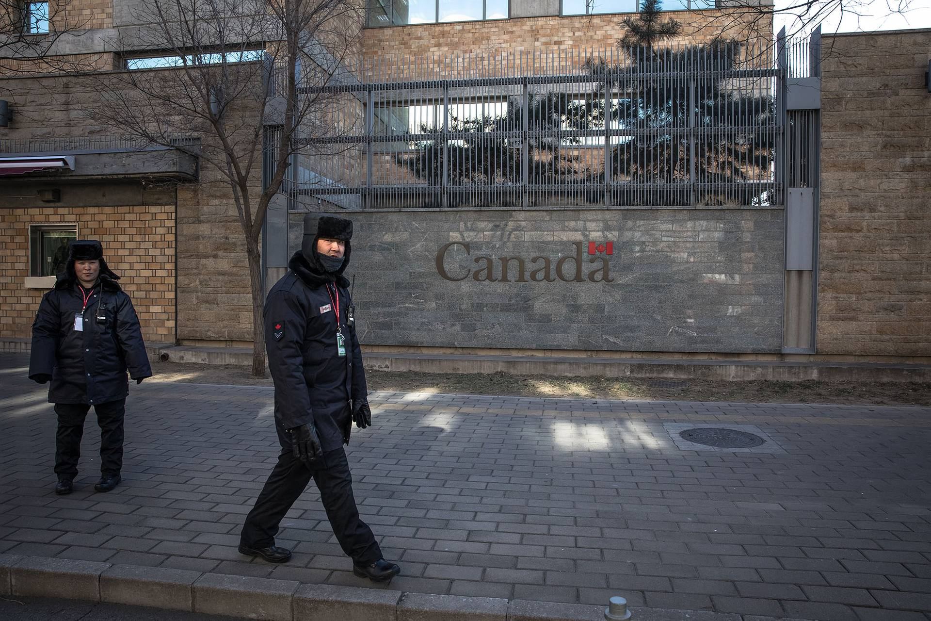Китайські охоронці біля посольства Канади в Пекіні, Китай, 15 січня 2019 року. Китайський суд виніс смертний вирок, замість 15 років ув'язнення, одному із канадійців, яких раніше звинуватили у контрабанді наркотиків. Це рішення суд міста Далянь прийняв після того, як розгорівся дипломатичний конфлікт між Канадою і Китаєм, а канадські правоохоронці на початку січня заарештували, на прохання США, дочку засновника китайської компанії Huawei, фінансову директорку Мен Ванчжоу у Ванкувері