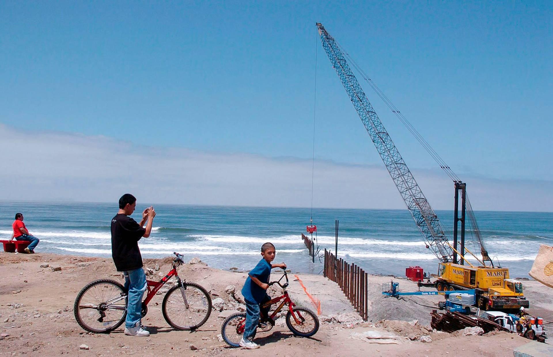 Мешканці району Плайяс-де-Тіхуана спостерігають за будівництвом прикордонної стіни між Мексикою та США, чстина якої на березі океану, Тіхуана, штат Баха-Каліфорнія, Мексика, 23 червня 2005 року. Залізні прути розділяють Тіхуану із каліфорнійським містом Сан-Дієго у США