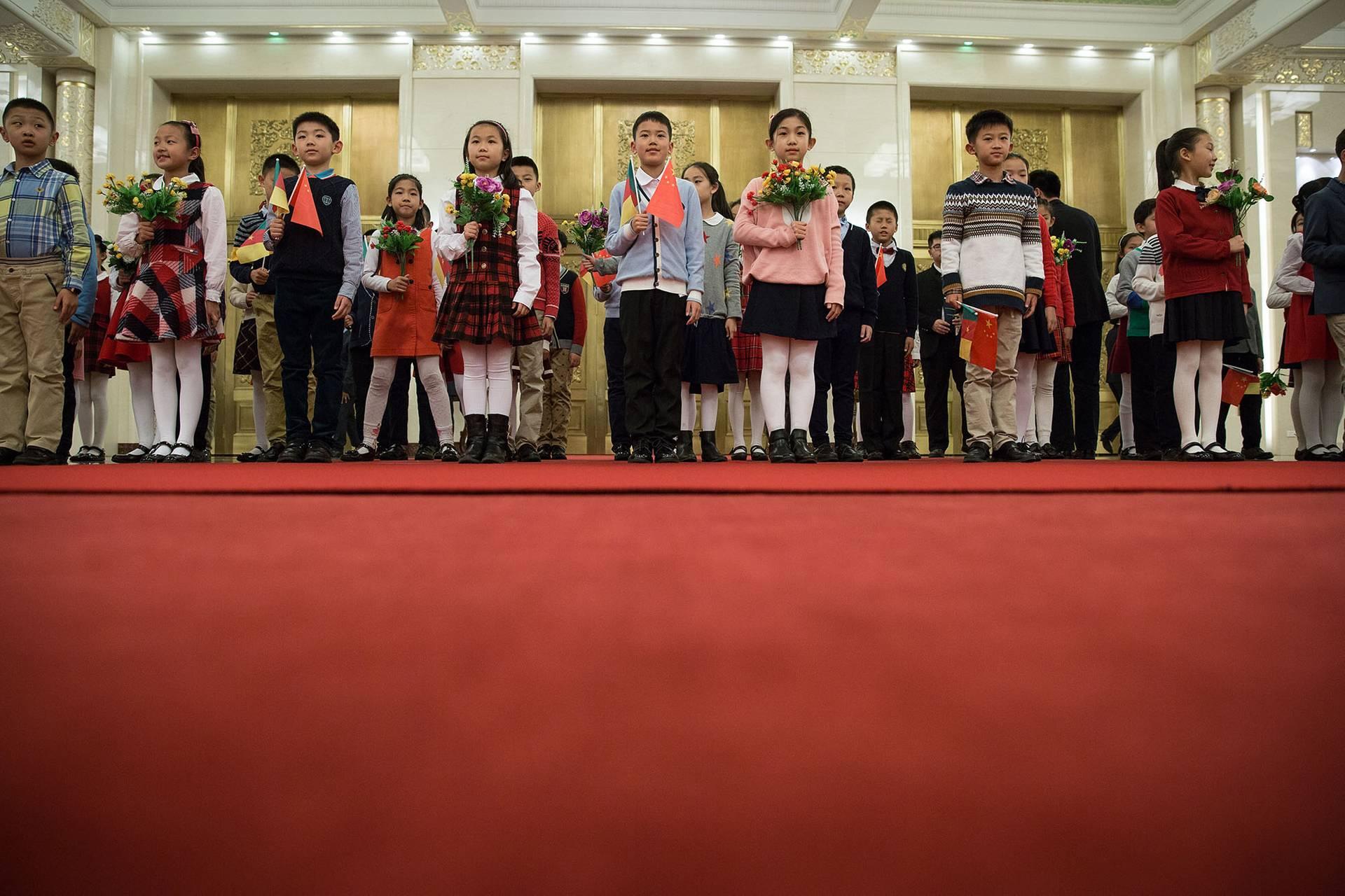 Десятиліттями комуністичним режимом в Китаї пропагувався образ ідеальної родини, в якій лише одна дитина (на фото — китайські діти тримають національні прапори Китаю та Камеруну на церемонії зустрічі президента Камеруну у Дімі народних зборів в Пекіні, Китай, 22 березня 2018 року)