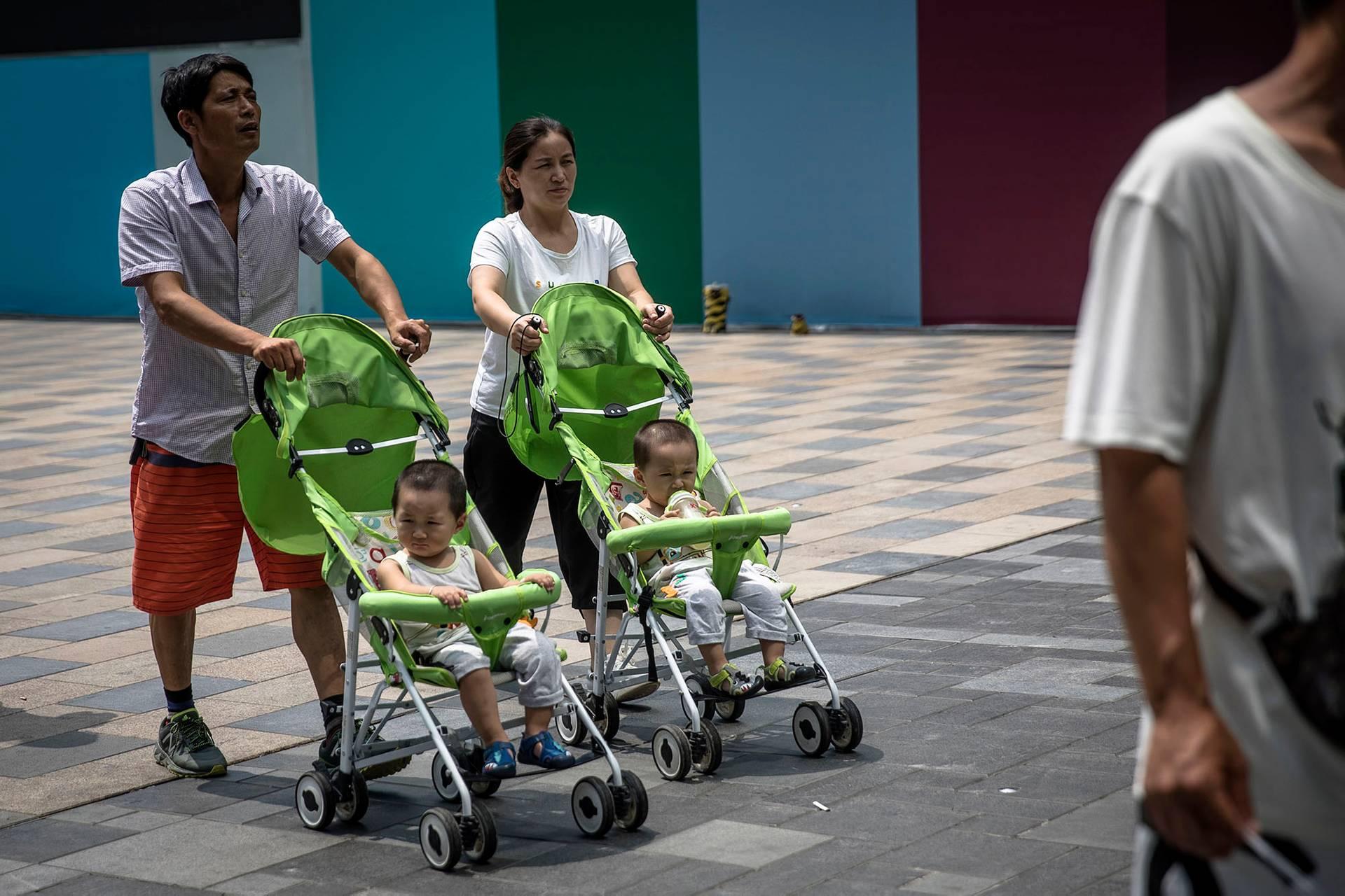 У 2016-му Компартія дозволила всім родинам мати по дві дитини, однак це не призвело до очікуваного бебі-буму (на фото — батьки із двома дітьми гуляють в районі Санлітун в Пекіні, Китай, 10 серпня 2018 року)