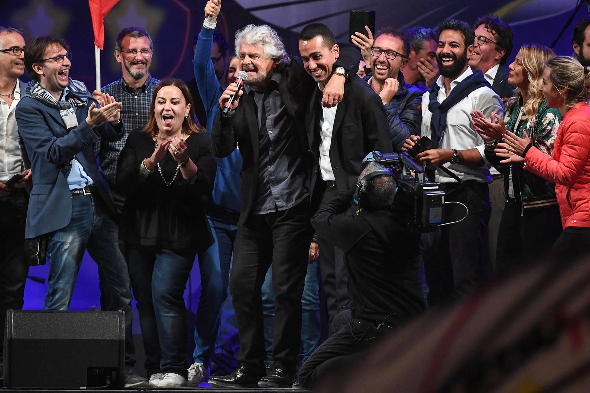 Лідер партії «Рух 5 зірок» і віце-прем'єр-міністр Італії Луїджі ді Майо (в центрі праворуч) обіймається на сцені із засновником партії та її ідеологом Беппе Грілло під час передвиборчого заходу у місті Ріміні, Італія, 23 вересня 2017 року