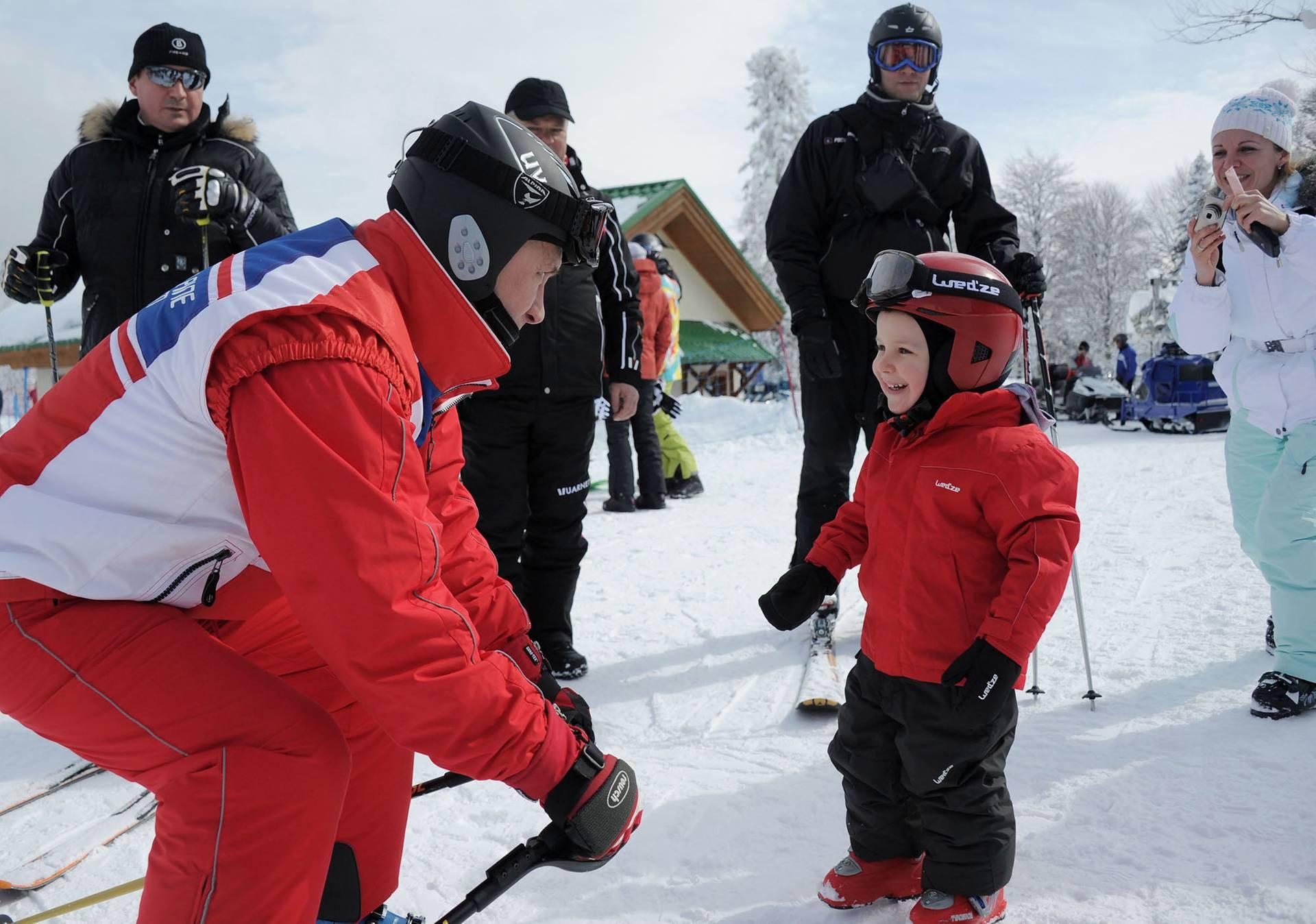 Президент Росії Володимир Путін (ліворуч) розмовляє з дитиною, коли готується до катання на гірськолижному курорті «Червона Поляна» у Сочі, Росія, 8 березня 2012 року