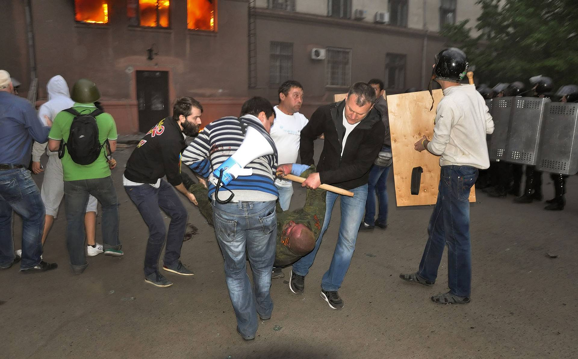 Люди намагаються допомогти пораненому проросійському активісту під час пожежі в будівлі Профспілок в Одесі, 2 травня 2014 року
