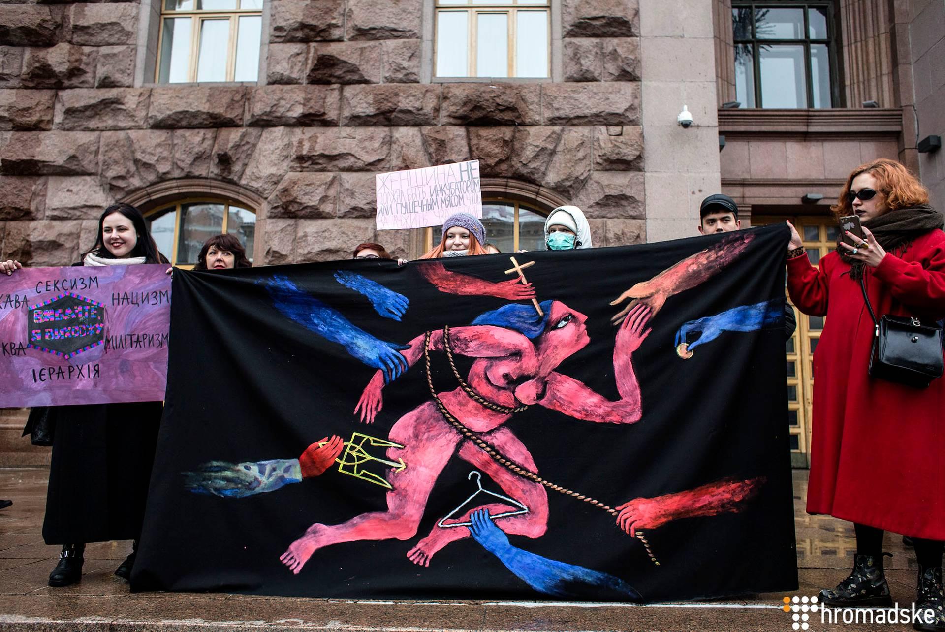Плакат художниці Дани Рваної на «Марші жінок» у Києві, 8 березня 2018 року. Авторка плакату на фото праворуч