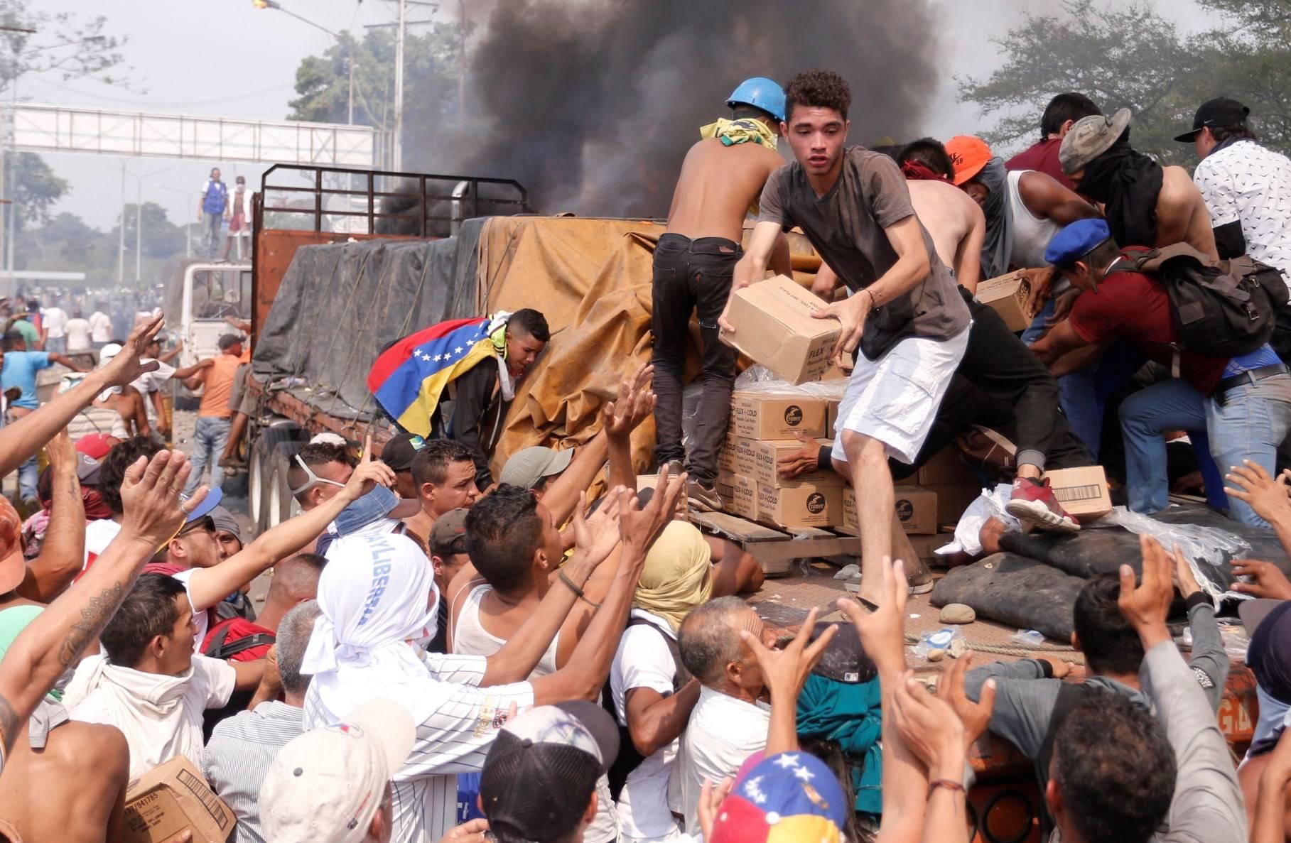 Люди намагаються врятувати частину гуманітарної допомоги з вантажівки, яка загорілась неподалік мосту Симона Болівара, що з'єднує Кукуту із містом Сан-Антоніо у венесуельському штаті Тачира, Венесуела, 23 лютого 2019 року
