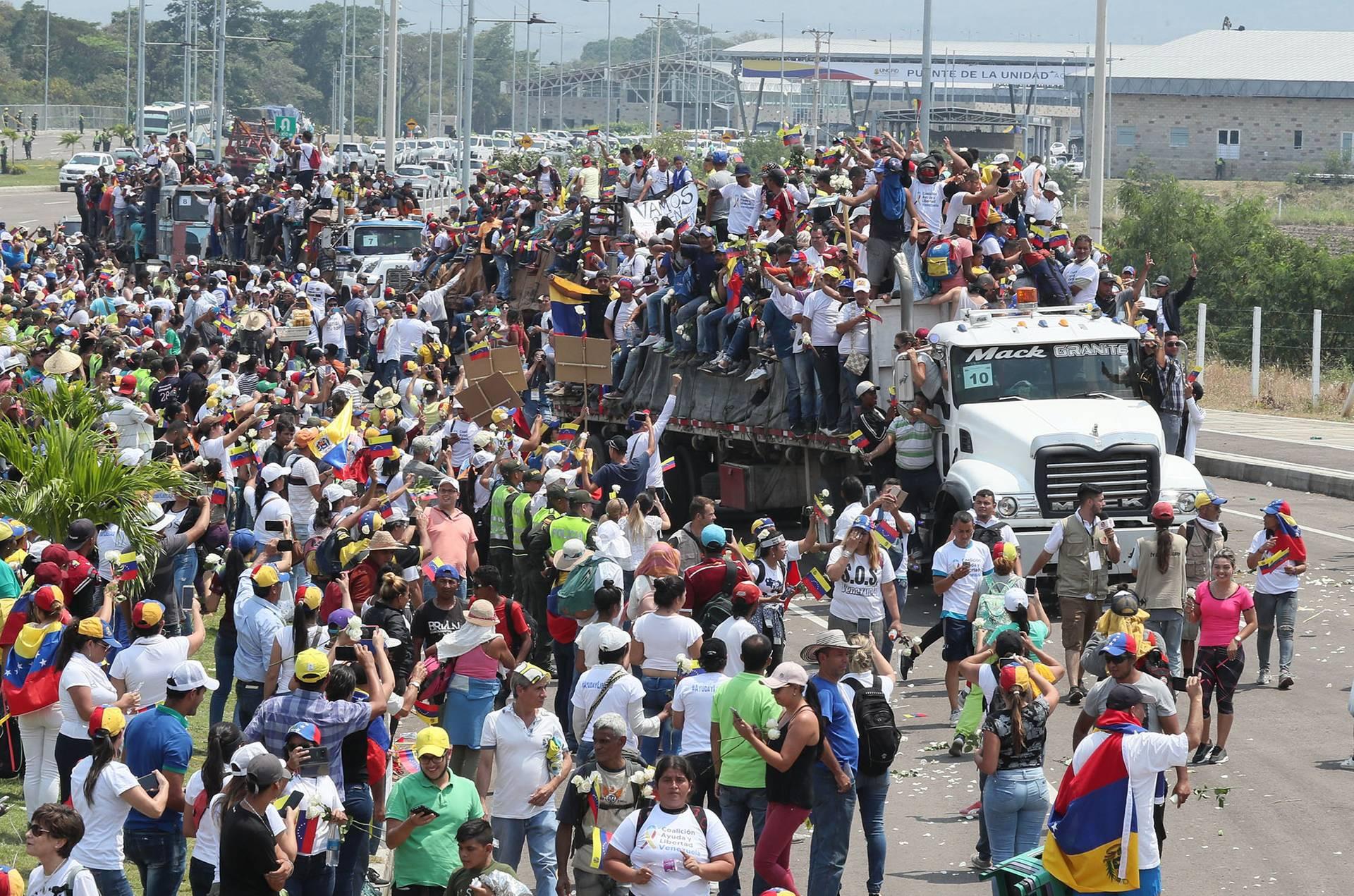 Активісти венесуельської оппозиції їдуть у вантажних автомобілях неподалік Кукути, Колумбія, 23 лютого 2019 року. Сотні венесуельців зібралися на колумбійській стороні біля моста Симона Болівара, що з'єднує Кукуту із містом Сан-Антоніо у венесуельському штаті Тачира, щоб сформувати живий коридор, який дозволить провезти гуманітарну допомогу у Венесуелу, Колумбія, 23 лютого 2019 року