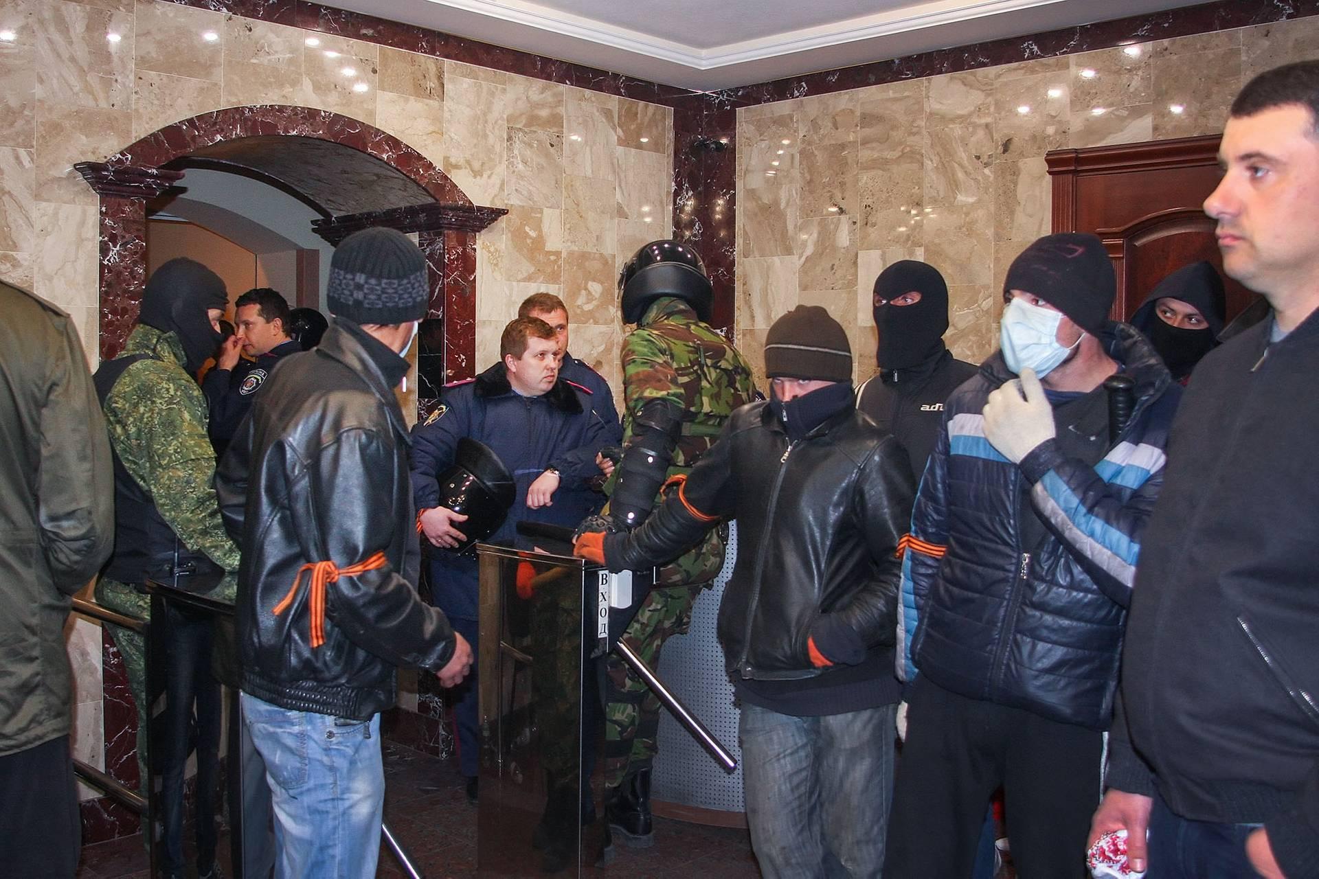 Озброєні чоловіки та міліціонери стоять у приміщенні регіонального донецького відділення МВС, захопленого проросійськими сепаратистами в Донецьку, 12 квітня 2014 року