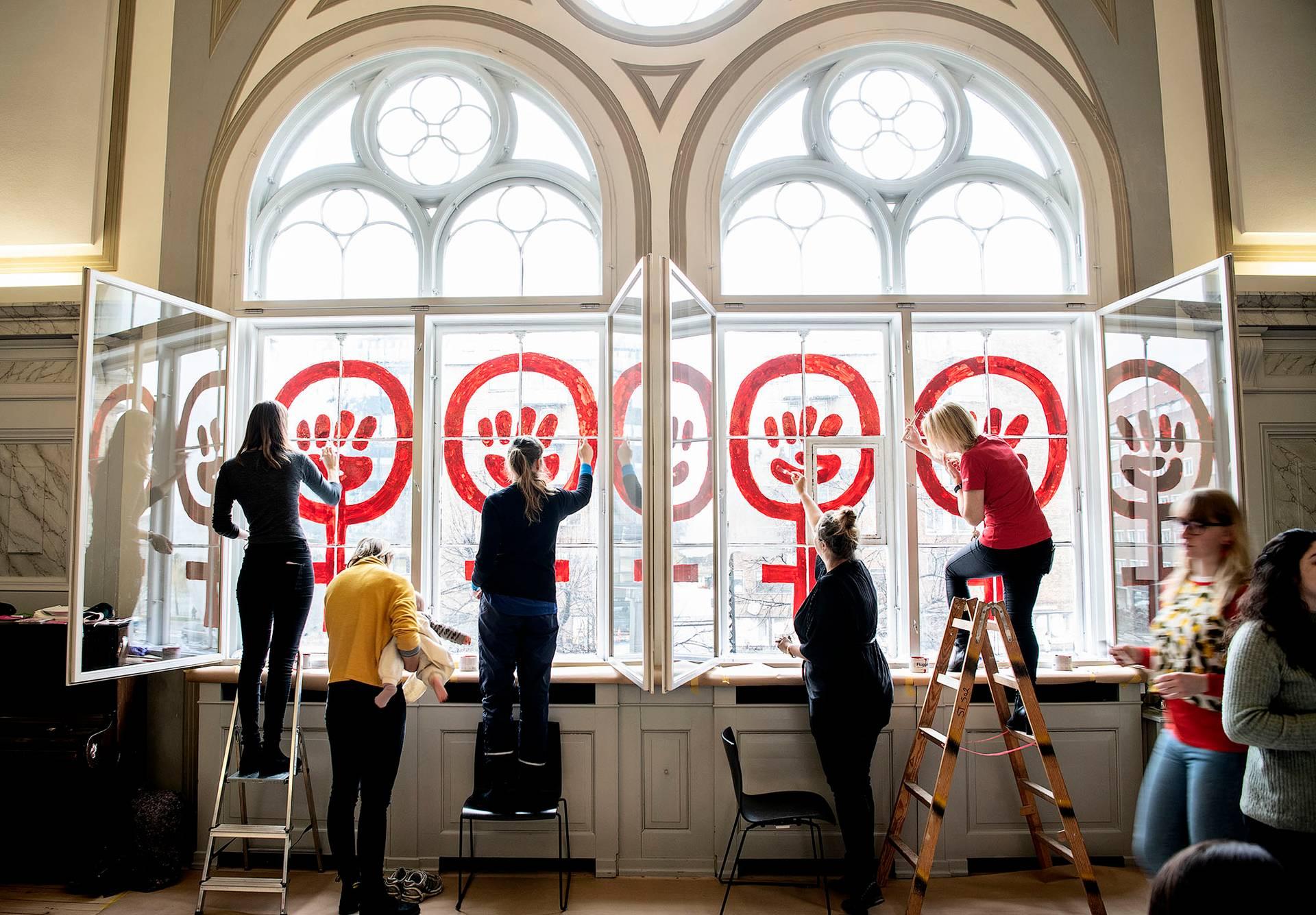 Данські жінки розмальовують вікна будівлі Danner Foundation у Копенгагені, Данія, 8 березня 2019 року. Цього року виповнюється 40 років відтоді, як жіночі символи були намальовані на вікнах в день, коли цей будинок зайняли 300 феміністок