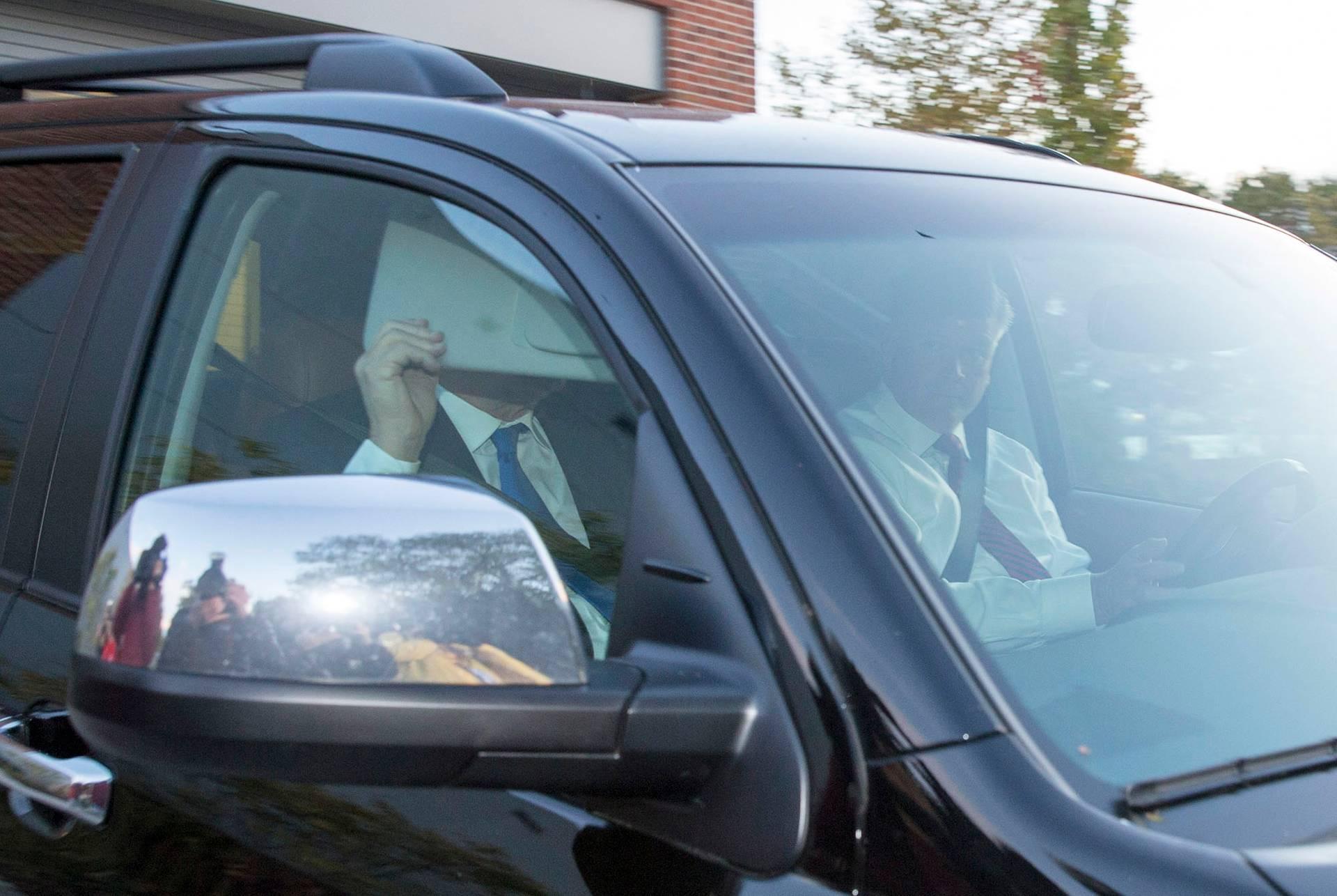 Пол Манафорт (ліворуч) ховає обличчя від фотокамер, коли виїздить з гаража власного будинку в Олександрії, штат Вірджинія, США, 30 жовтня 2017 року