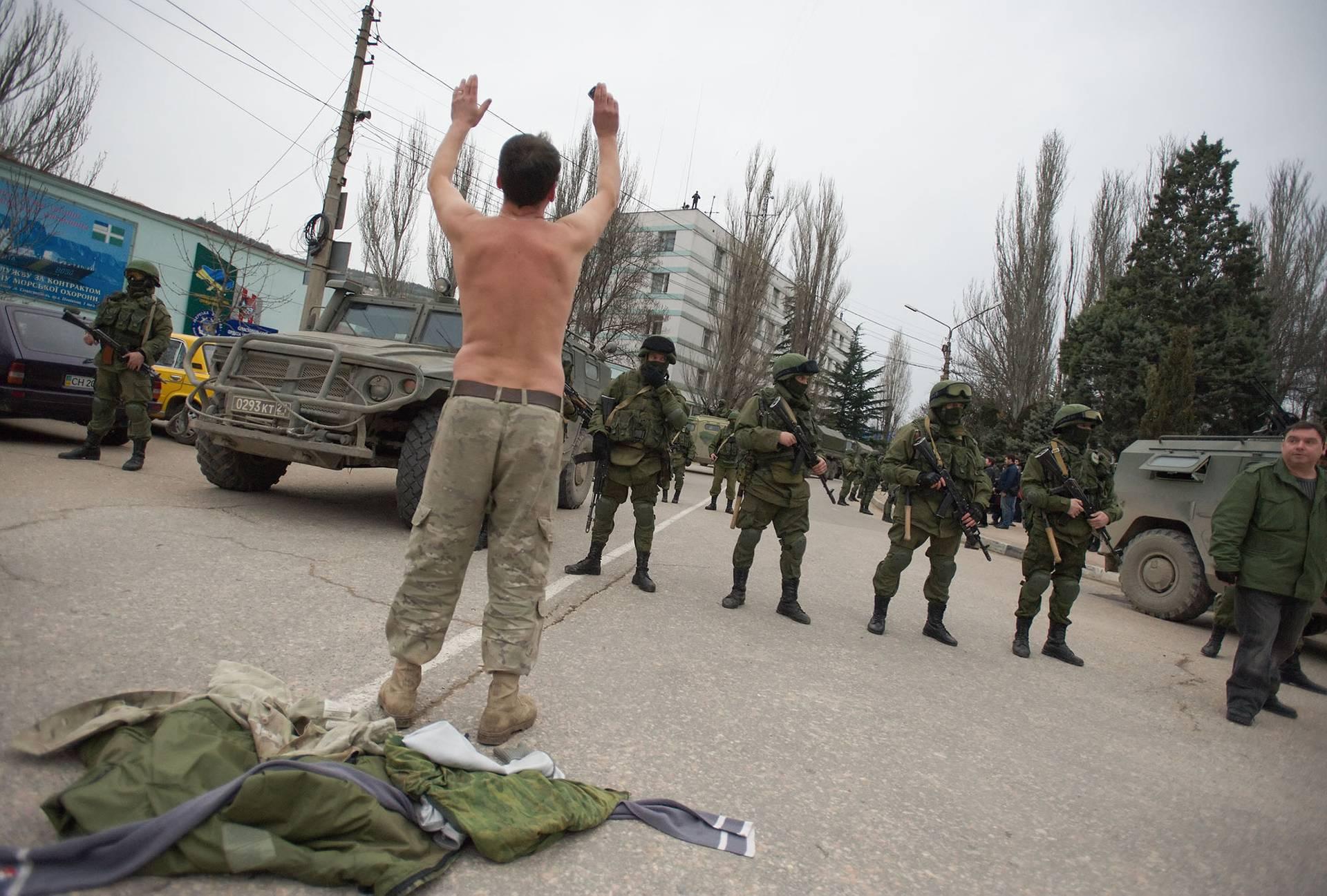 Український військовий намагається стримати і поговорити із озброєними російськими спецпризначенцями біля в'їзду на українську військову базу у Балаклаві, знявши одяг на знак того, що він не озброєний, Крим, 1 березня 2014 року