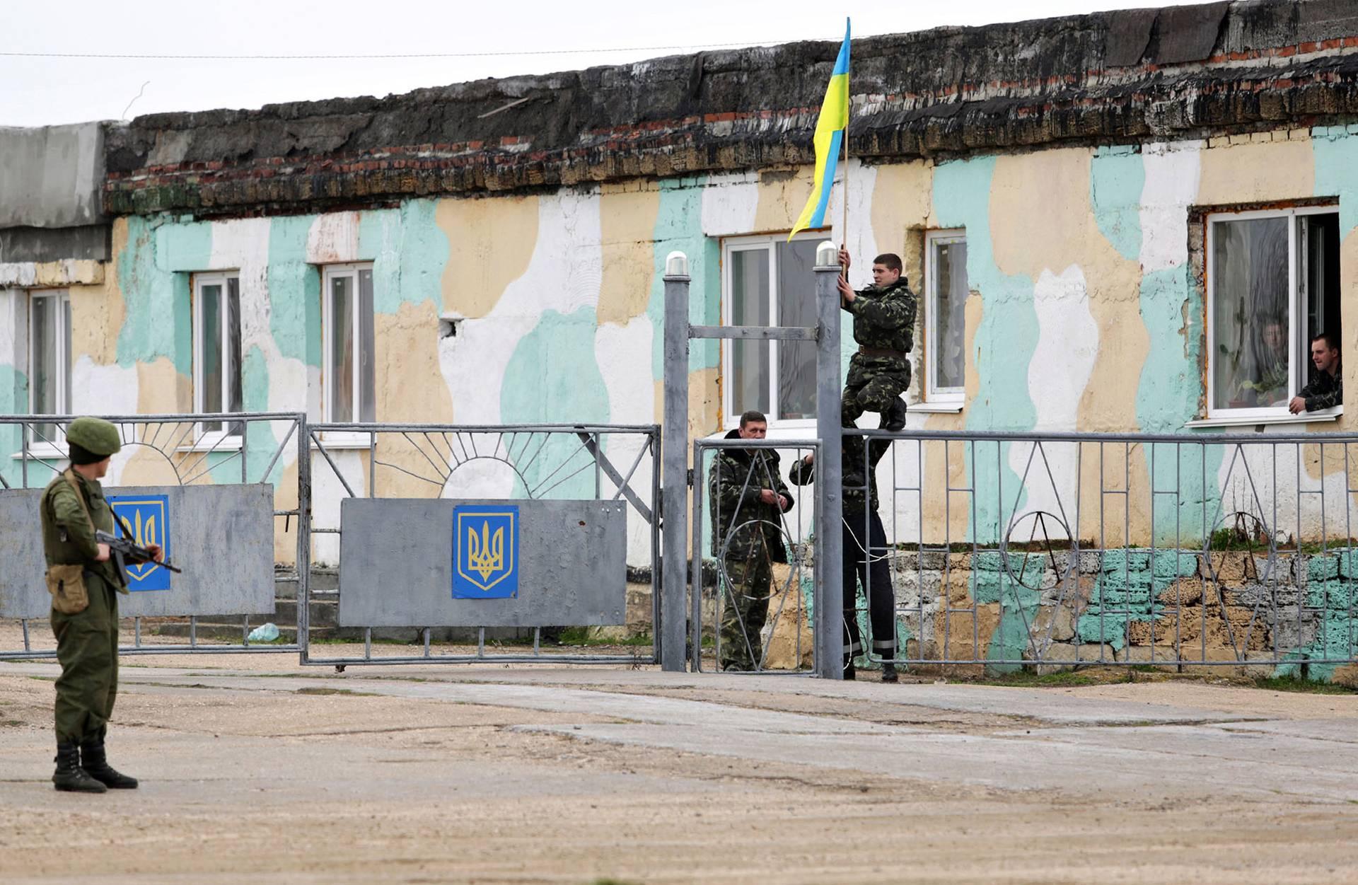 Українські військові піднімають український прапор на флагшток біля входу до військової бази у у Бельбеку неподалік Севастополя, Крим, 4 березня 2014 року