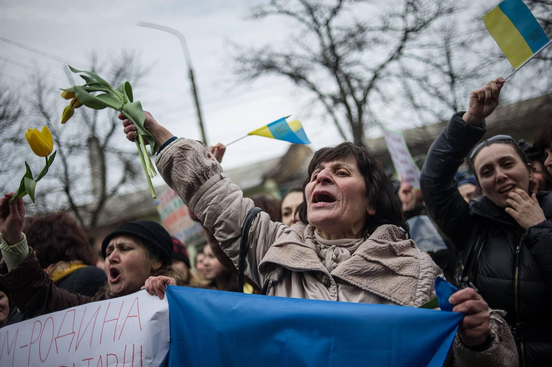 Жінки тримають квіти і українську національну символіку під час проукраїнського мітингу в Сімферополі в Міжнародний день прав жінок, Крим, 8 березня 2014 року