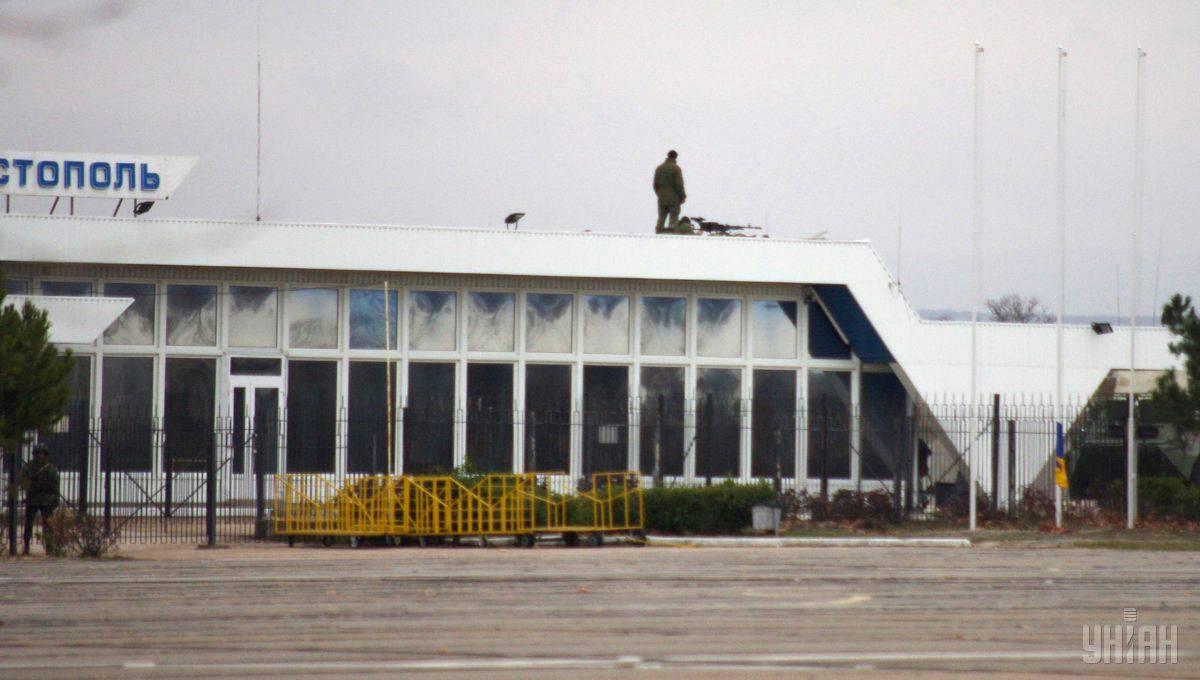 Військовий зі зброєю на даху аеропорту «Бельбек» біля Севастополя, Крим, 28 лютого 2014 року. Близько півтора десятка військових вантажівок з озброєними російськими військовими заблокували аеропорт «Бельбек» вночі 27 лютого