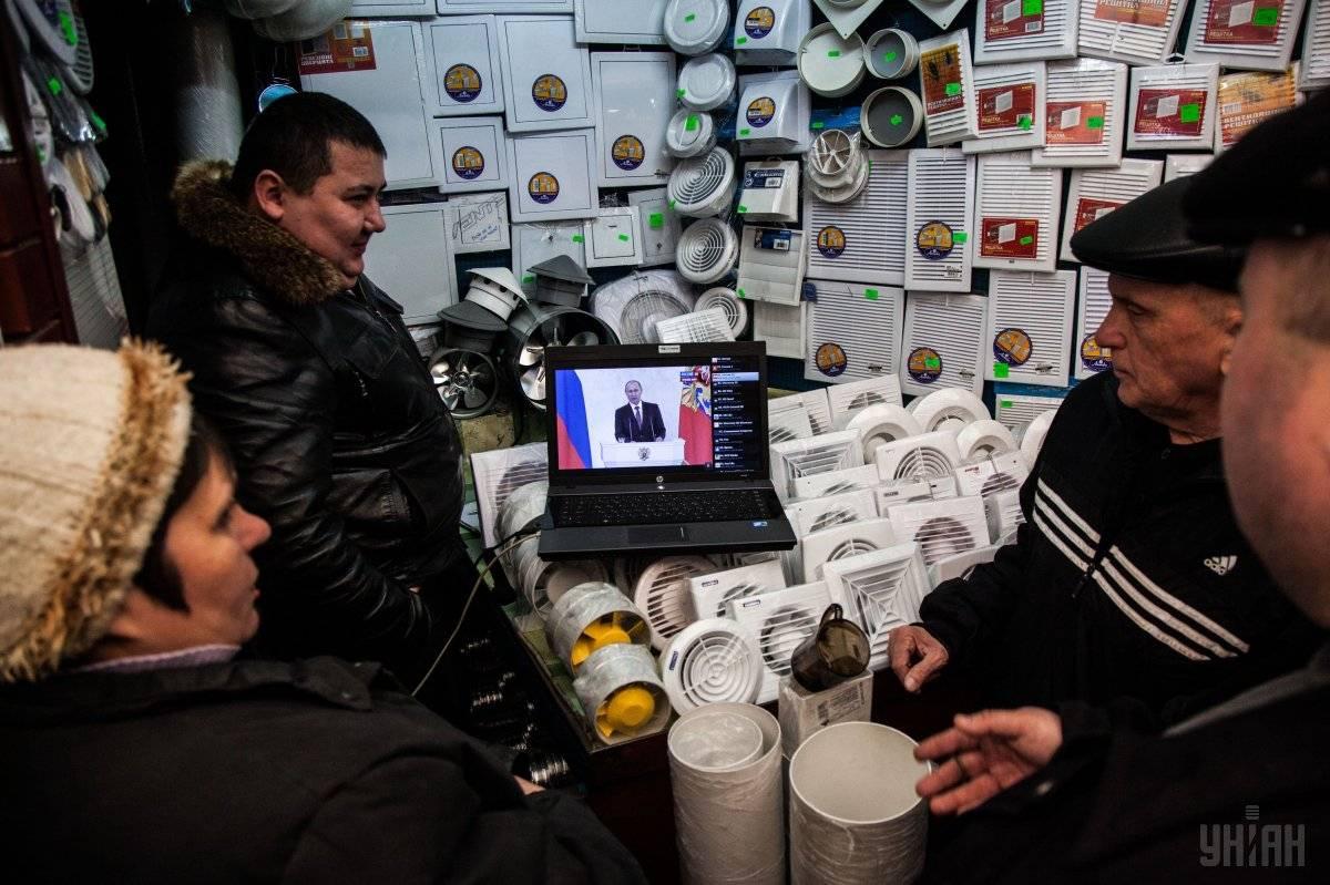 Люди дивляться трансляцію прес-конференції президента Росії Володимира Путіна на ринку у Сімферополі, Крим, 18 березня 2014 року