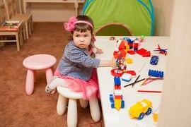 Малышка за столом с развивающими игрушками в детском клубе Канарейка