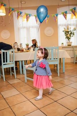 Счастливая девочка с воздушным шариком на празднике