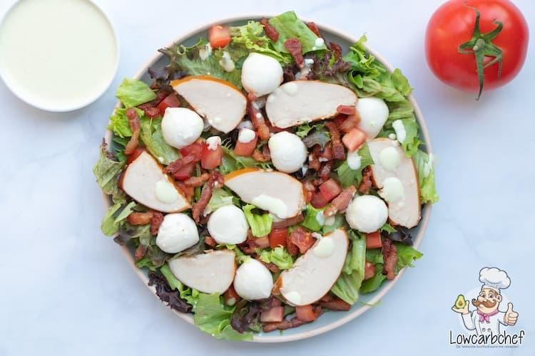 Salade met gerookte kip, mozzarella en spekjes.