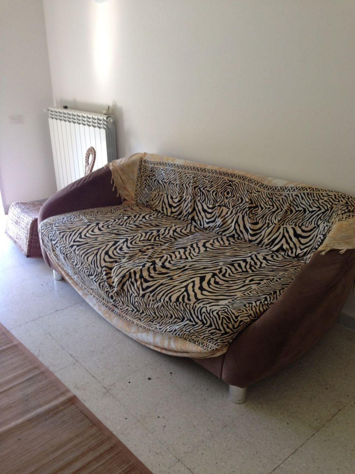 Un divano marrone biposto due piccole sedie a dondolo in for Divano a dondolo