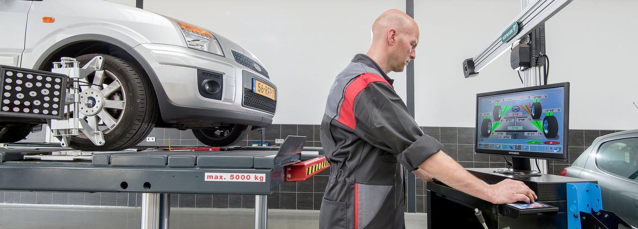 Monteur staat achter een computer waar op te zien is of een auto goed is uitgelijnd.