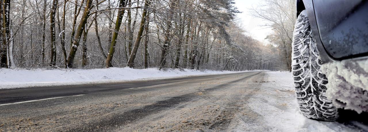 Weg met sneeuw waar een rijdende autoband op de voorgrond staat