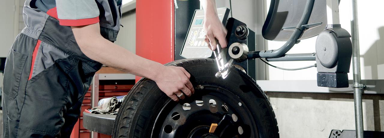 Een monteur is met een daarvoor bestemd apparaat een autoband aan het uibalanceren.