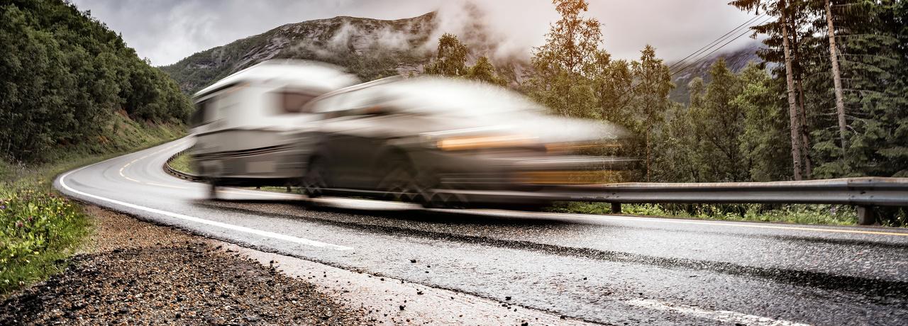 Een auto met een caravan erachter die op een bergweg naar beneden rijdt op en regenachtige dag