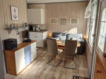 Wohnbereich mit Couch, Esstisch, offener Küche, Fernseher und DVD-Player
