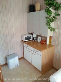 Wohnbereich mit offener Küchenecke, ausgestattet mit zwei Kochplatten, Kühlschrank, Toaster, etc.