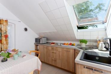 Die separate Küche mit Induktionskochfeld, Mikrowelle (mit Grillfunktion), Kühlschrank mit Gefrierfach, ...