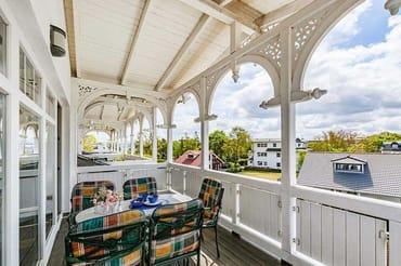 großer überdachter Balkon mit Tisch und Stühlen