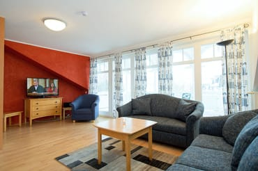 Sitzecke mit großem TV und Balkon