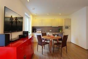 Das Wohnzimmer überzeugt mit gemütlichem Ecksofa, Flachbild-TV sowie einer mit allen Extras ausgestatteten Einbauküche. Bodentiefe Fenster geben dem WZ eine lichtdurchflutete Atmosphäre.