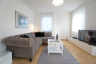 Wohnzimmer mit Eckcouch und Smart-TV