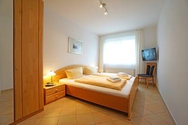 Schlafzimmer mit Doppelbett und Fernseher