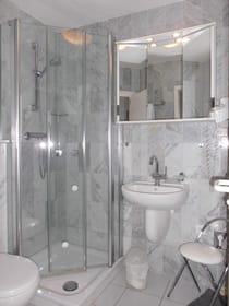 Das Duschbad. Die Dusche mit niedrigem Einstieg, Haltegriff und kleiner Ablage.
